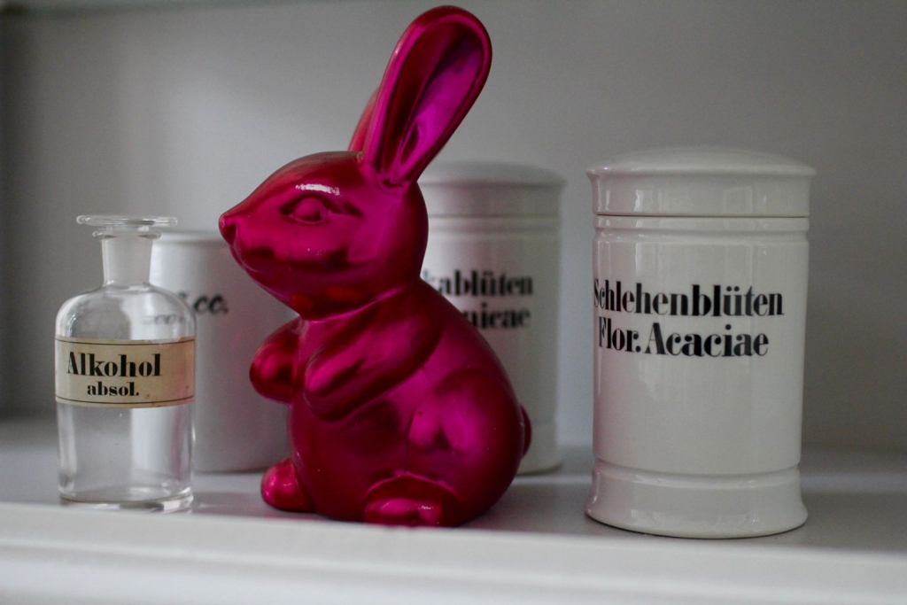 Ein magentafarbener Hase sitzt vor weißen Apothekergefäßen aus Keramik mit der Aufschrift Schlehenblüten, Arnikablüten und Alkohol. das Bild wird auf der Seite über Burnout verwendet.